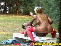 Lusty shemale in red stockings bending down her boyfriend for outdoor anal