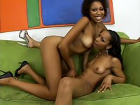 A couple of sexy black girls enjoy sticking a long glass dildo into each others\' pussies