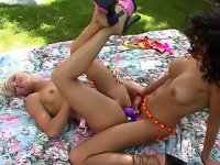 A couple of slim lesbians fucking each other in the ass with a massive strap-on outdoors